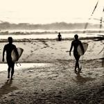 surfers entering water